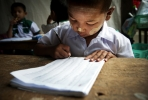 A young boy learns to write in a Burmese kindergarten class. Photo by UN Photo on flickr.