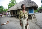 A Timorese women stands in front of traditional housing. Photo by UN Photo on flickr.
