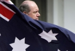 Defence Minister David Johnston stands behind an Australian flag - and the navy. Photo by AFP.
