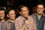 Jokowi with checkered shirt and microphone. Photo by AFP.