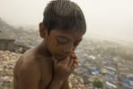 A young boy stands on rubbish in Mumbai's slums. Photo by Brett Davies on flickr.