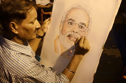 An artist draws a portrait of India's new Prime Minister Narendra Modi. Can some shrewd political moves recast his conservative image? Photo by AFP.